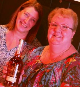 Jean Claffey and Deirdre Grant (both Joe Walsh Tours) with her bottle of Bourbon